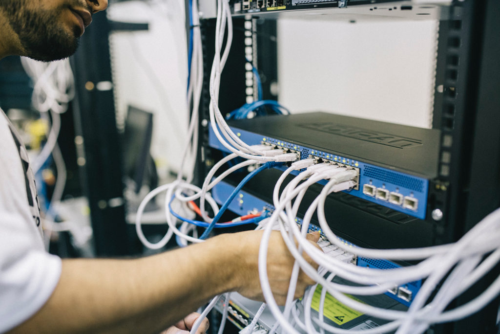 Engineer Working In Network Rack